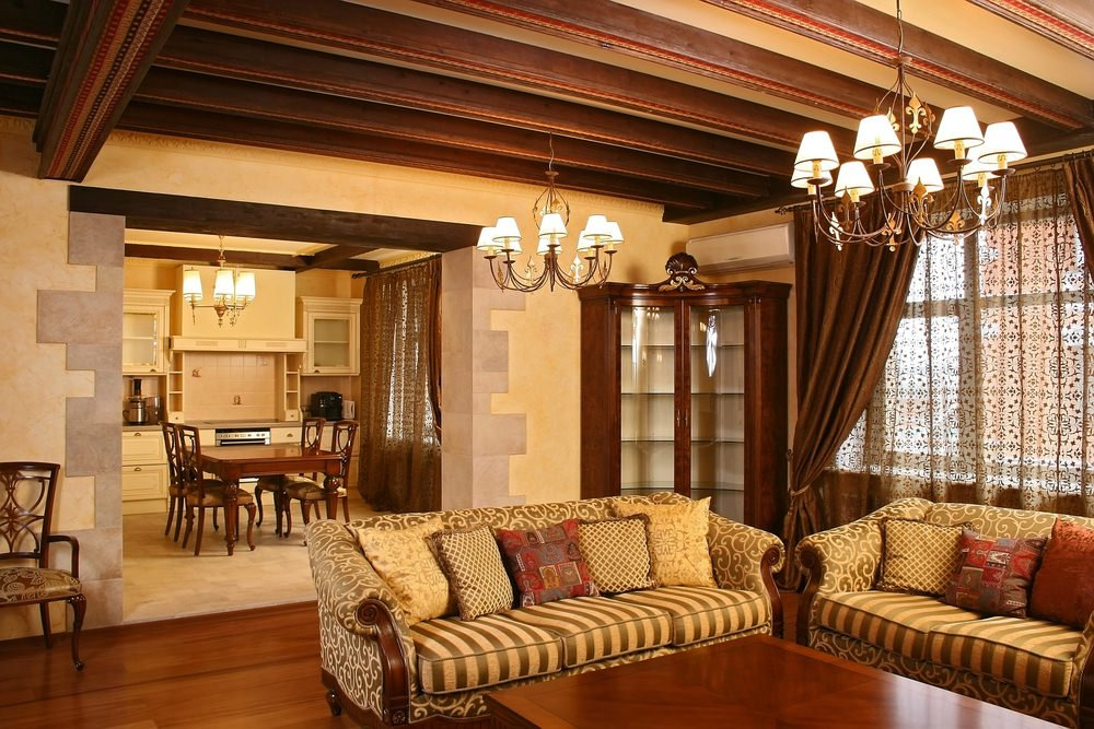 A classy formal living room boasting a nice set of seats lighted by a couple of gorgeous chandeliers.