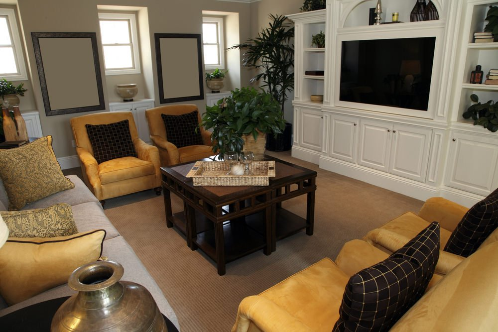 Charming living room offers a dark wood coffee table surrounded with mustard yellow armchairs and a gray sectional over carpet flooring.