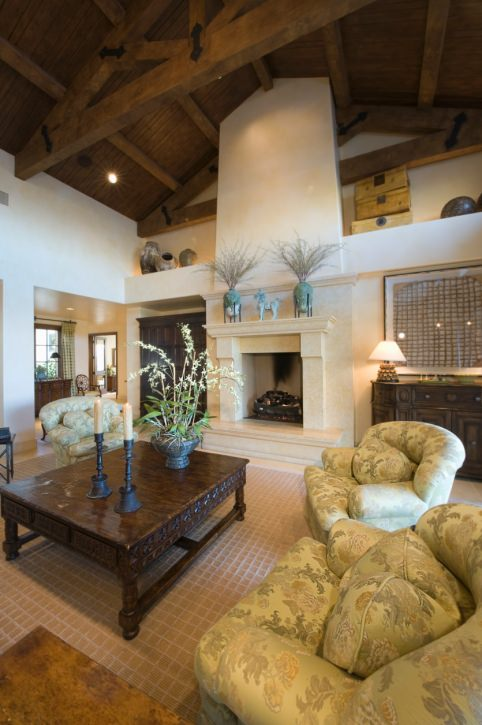 This formal living room offers elegant seats and a fireplace, along with a wooden tall ceiling with beams.