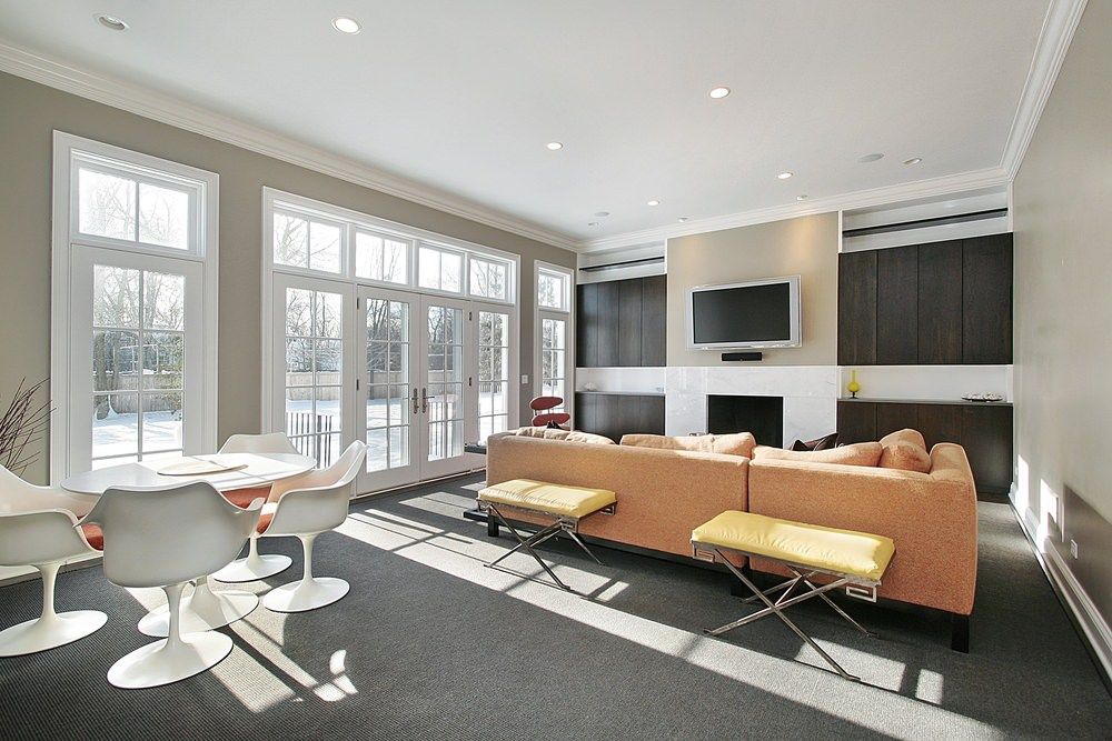 A living space featuring a beige sofa set together with a fireplace and a round dining nook set on top of the gray carpet flooring.