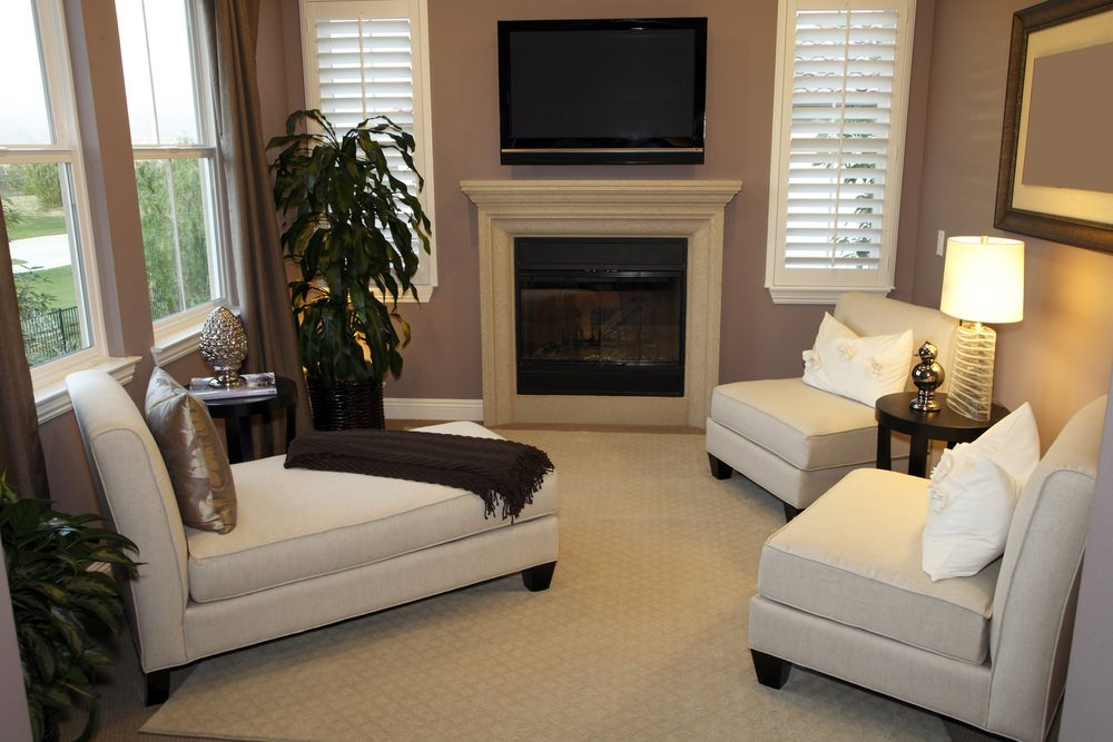 Gray living room with sleek white chaise lounge and chairs facing the fireplace fixed below the television.