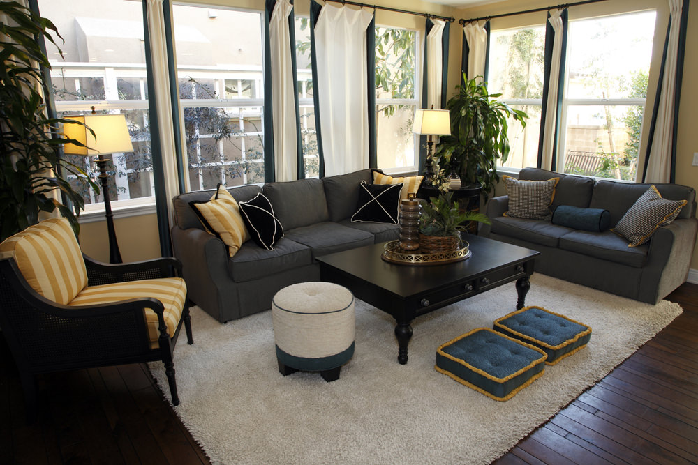 This living room features gray sofas with black coffee table and yellow striped accent chair. There are ottomans that lay on a gray shaggy rug over dark wood plank flooring.