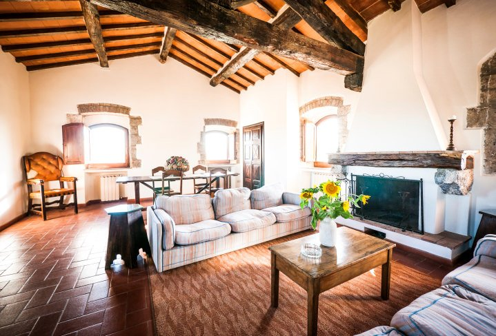 This formal living room boasts red tiles floors and a wooden ceiling with large exposed beams. The room also offers a fireplace.