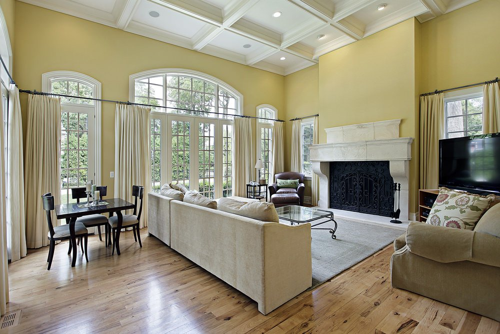 A classy living space featuring yellow walls and hardwood floors, along with a large fireplace and a comfy sofa set.
