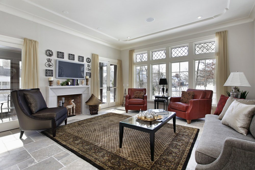 This living room boasts a set of elegant seats and rug set on the tiles flooring. The TV and the fireplace look glamorous together.