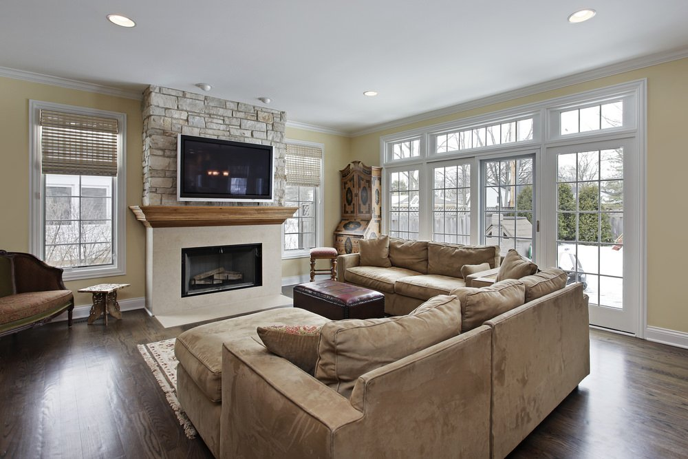Spacious living room featuring a cozy sofa set and a large fireplace with a TV on the brick wall. The hardwood flooring looks perfect together with the room's style.