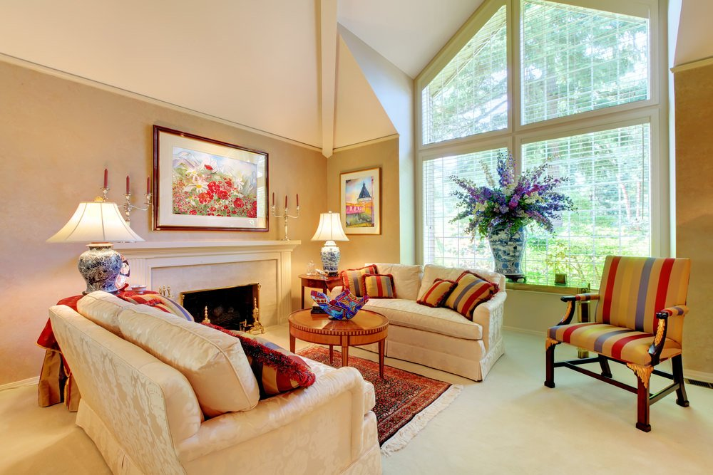Small living space featuring white tiles flooring matching the classy white couches along with a fireplace.