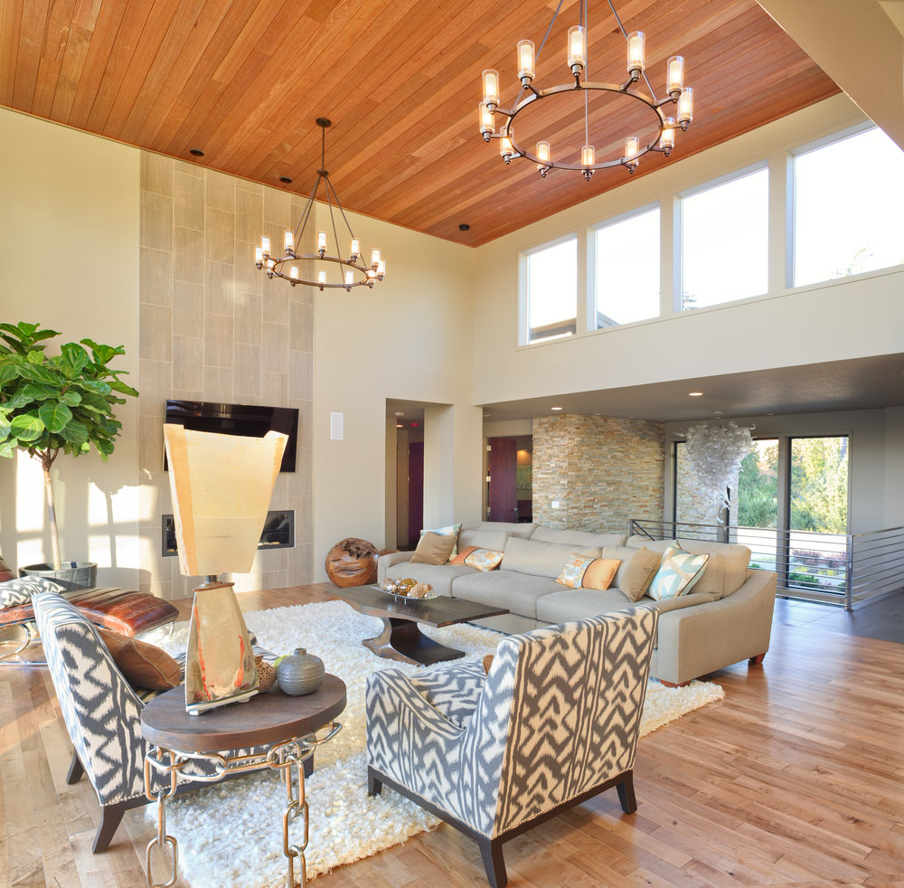 A formal living space featuring a cozy set of seats and a white rug covering the hardwood flooring. The area also has a fireplace and a large widescreen TV on the wall.