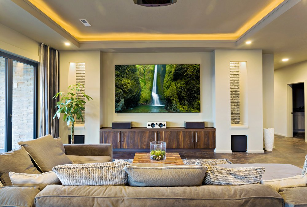 White living room offers a flat panel display mounted above the wooden TV stand topped with speakers and in between inset wall niche.
