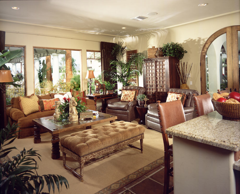 Classic living room boasts a brown skirted sofa and leather armchairs along with a wooden coffee table and tufted ottoman.