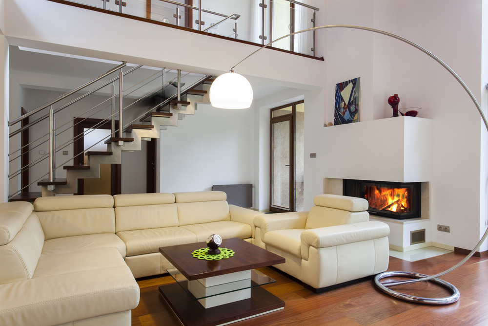 Modern living space featuring a cream sofa set with a stylish center table along with a modish fireplace.