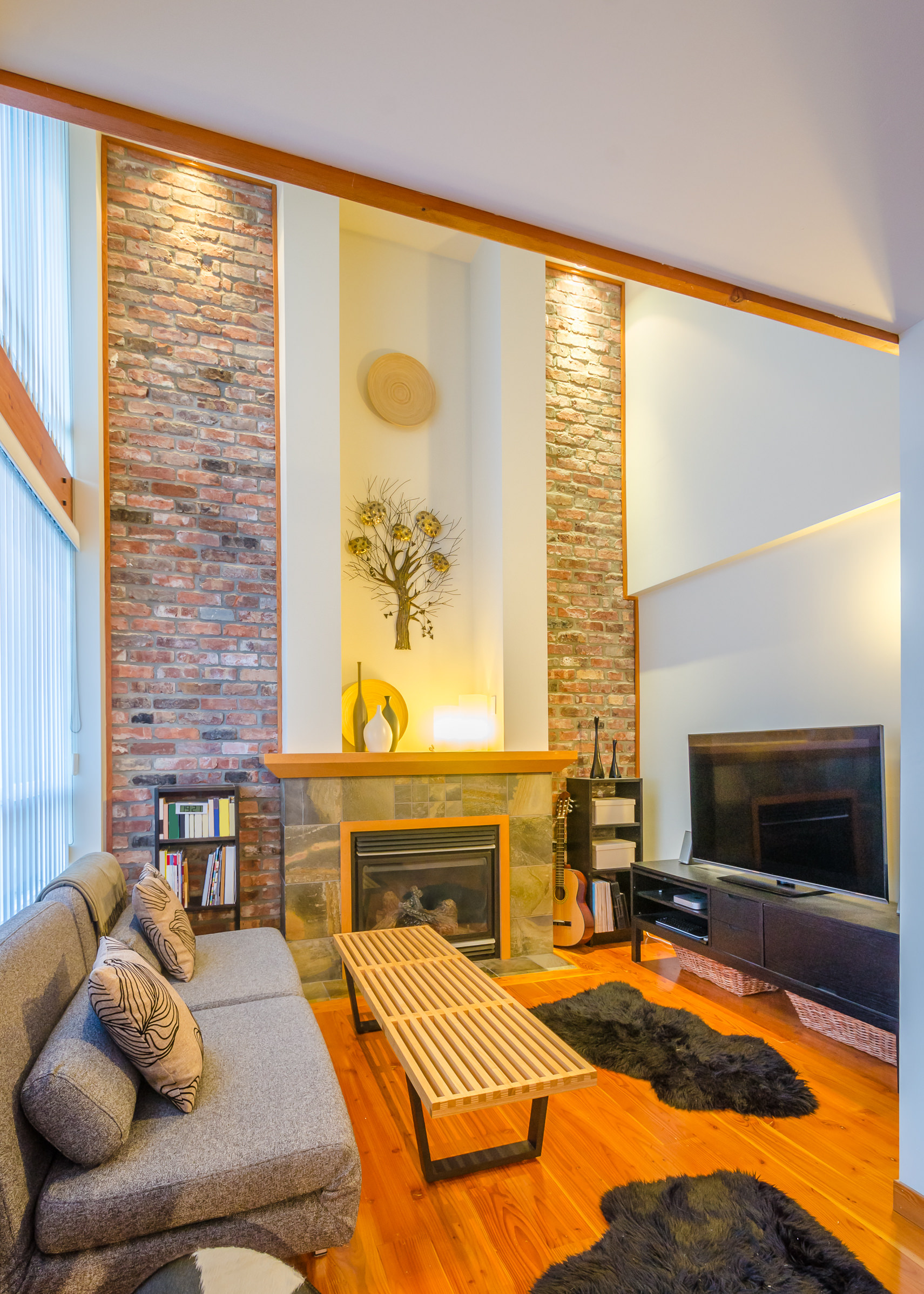A small living space featuring a fireplace, a comfy sofa set and a large widescreen TV in front.