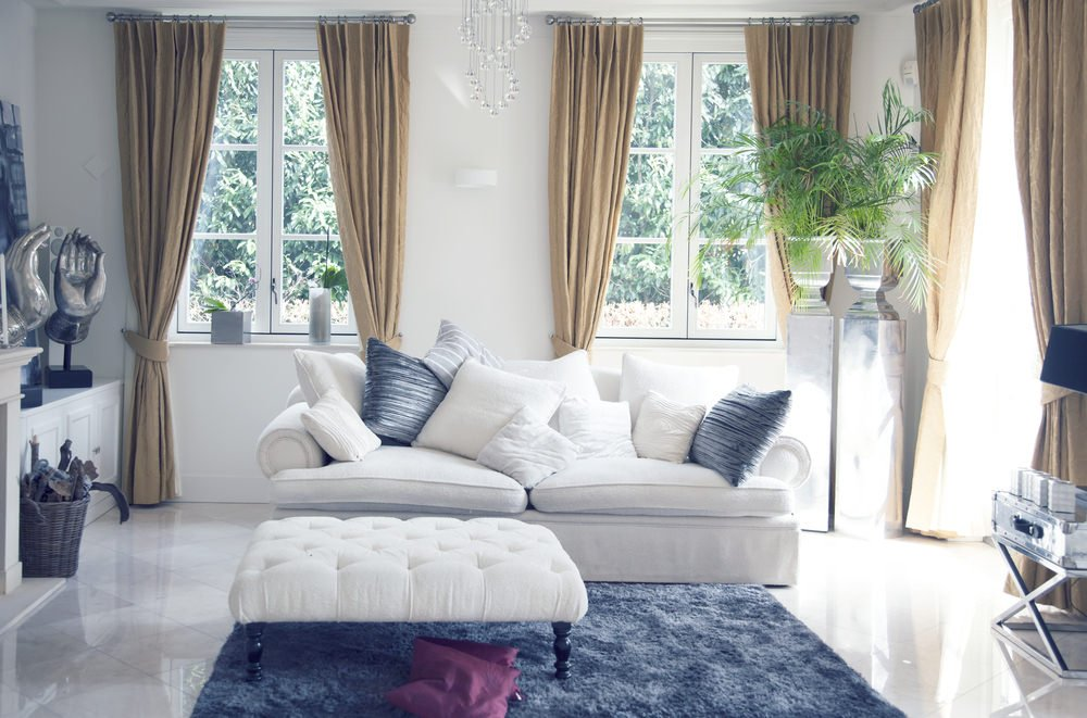 Classy living room with white walls and couch along with a stylish rug set on a sparkling tiles flooring.