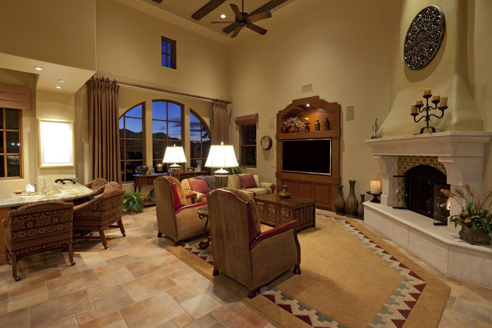 Mediterranean great room with a classy living space with a fireplace, and a beautiful dining set. The high ceiling features exposed beams.