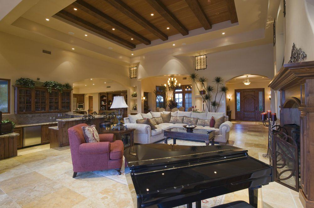 Large great room featuring classy tiles flooring and high tray ceiling lighted by scattered recessed lights.