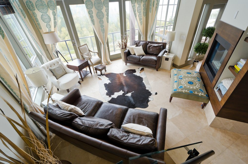 An elegant living room with classy leather couch and a rug set on the tiles flooring.