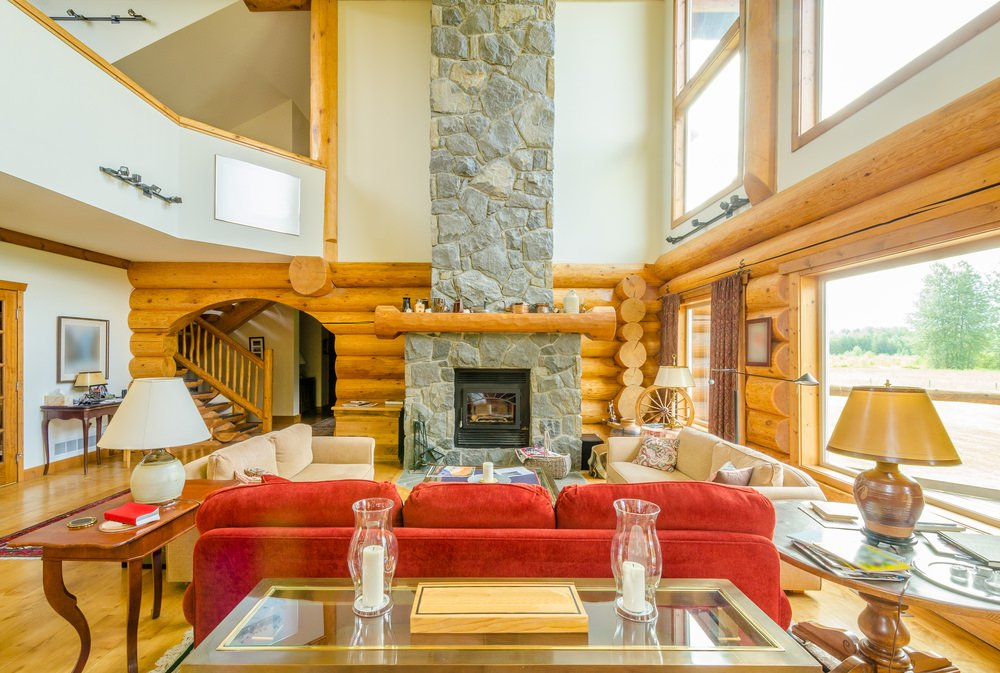 A rustic living room featuring a stone fireplace and a stylish set of seats under the tall ceiling.