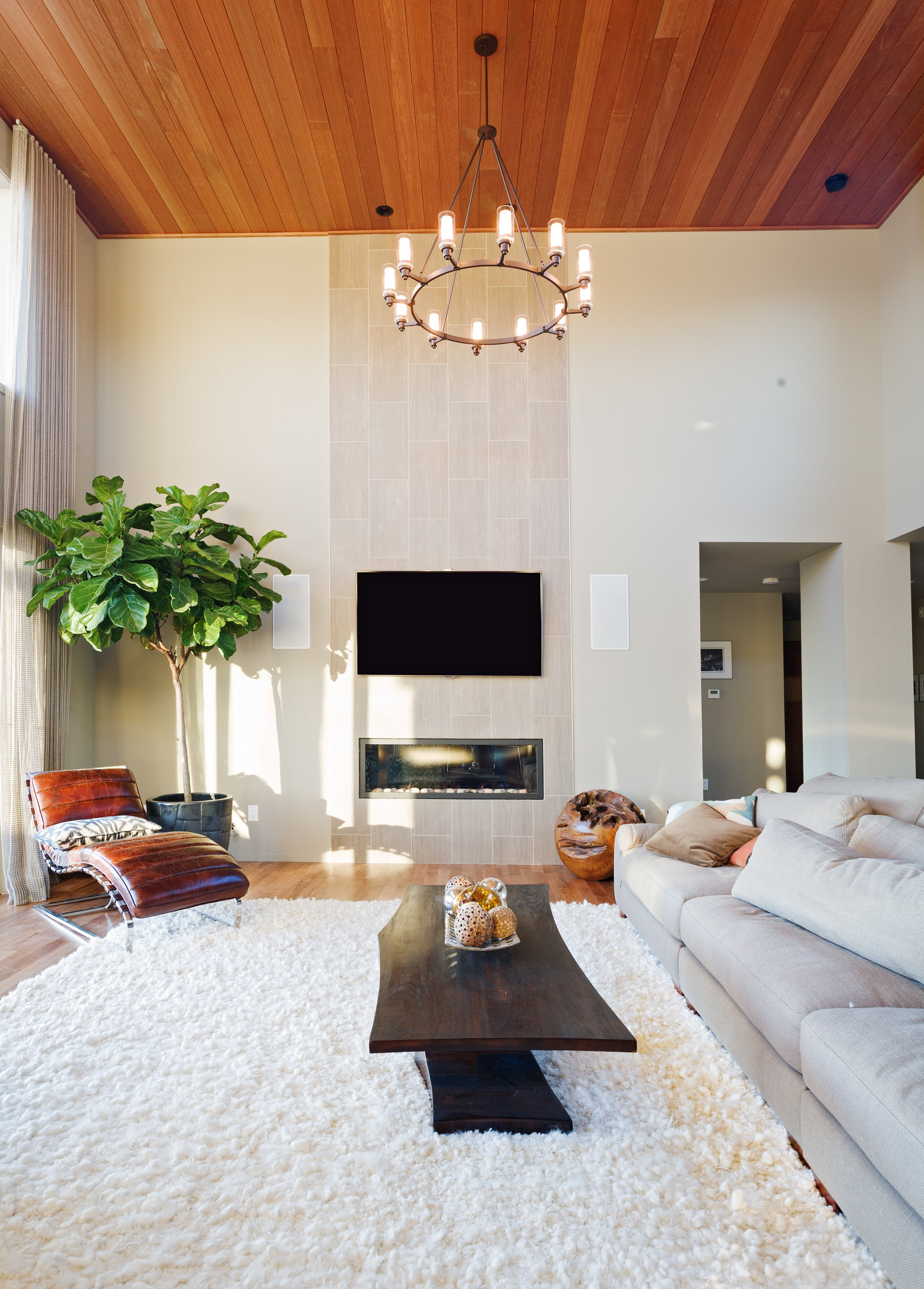 This living space features a long gray couch and a white rug along with a center table and a fireplace under the home's tall ceiling.