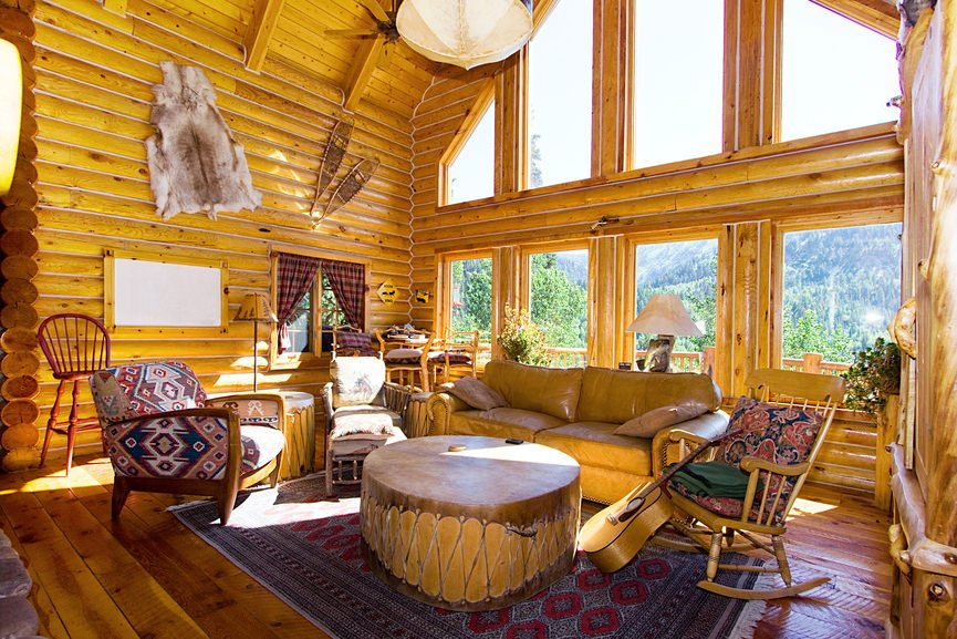 Rustic living space featuring a nice set of seats and a tall ceiling. The room also has a large area rug and glass windows.