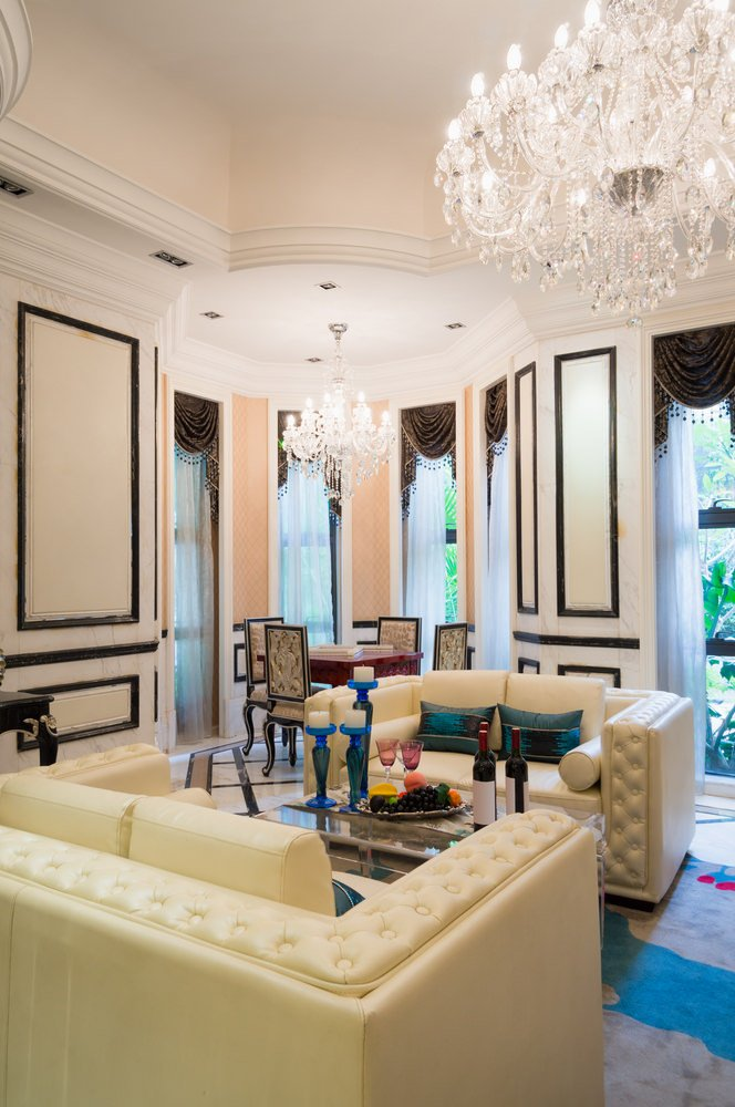 This great room offers a cozy living room set and a classy dining table set, both lighted by a pair of glamorous chandelier lights.