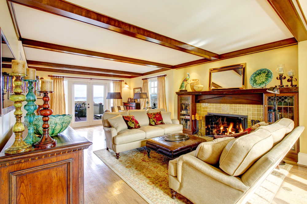 Spacious master bedroom with classy sofa set near the large fireplace. The room is surrounded with beige walls.