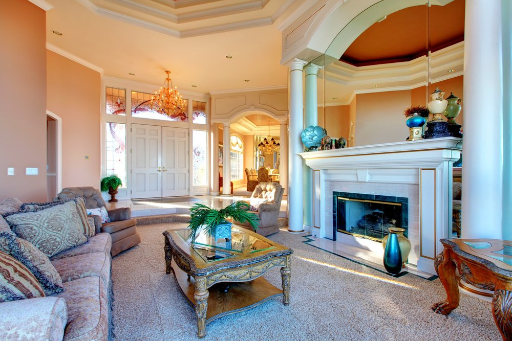Large Mediterranean living room boasting a large fireplace paired with elegant seats along with a lovely carpet flooring. The center table looks absolutely elegant together with the chandelier.