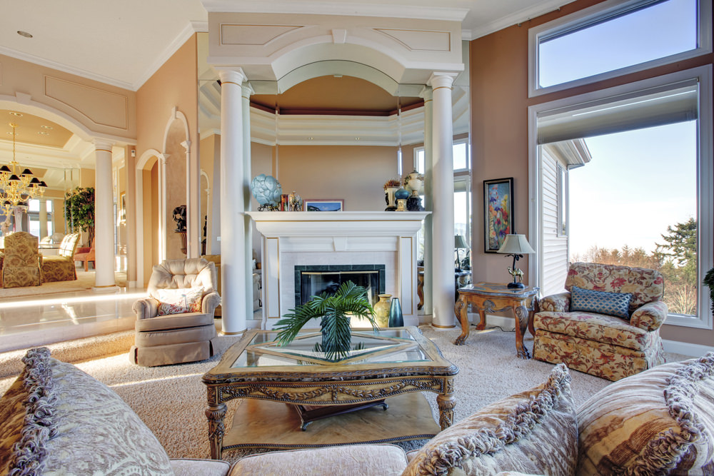This living room boasts elegant seats and a large and classy center table set on the home's carpet flooring. The room also offers a large fireplace.