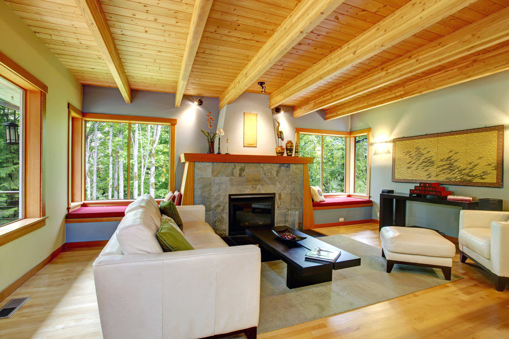Medium-sized formal living room with white seats and a large fireplace. The room features hardwood floors and wooden ceiling.