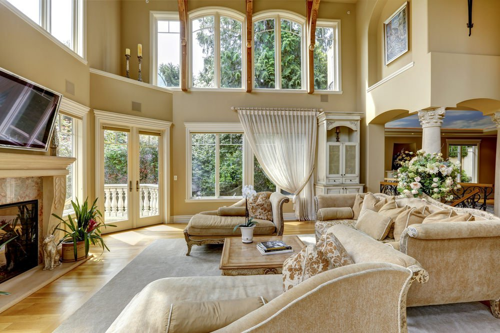 An open concept living room featuring elegant seats and a large fireplace with a widescreen TV on top of it. The living space is under the home's tall ceiling with exposed beams.