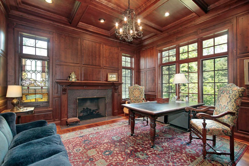 An elegant formal living room with stunning walls and coffered ceiling along with the reddish hardwood flooring topped by an attractive rug.