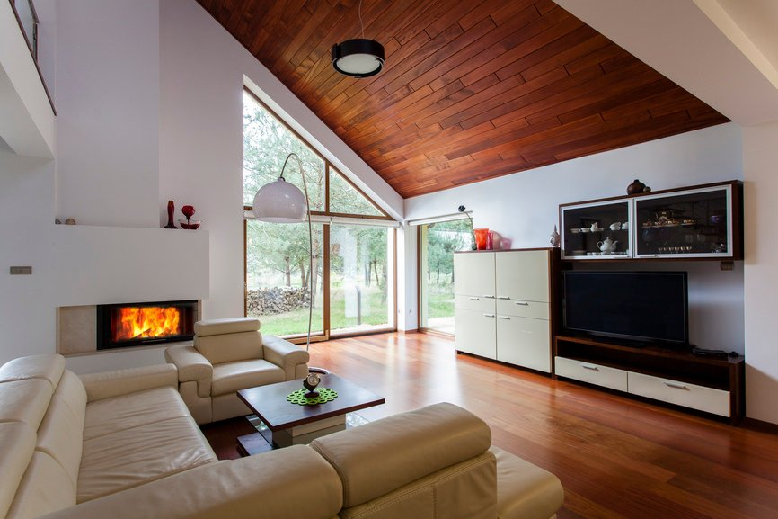 This formal living room offers a stunning fireplace on the side of the classy set of seats on top of the hardwood flooring matching the shed ceiling.