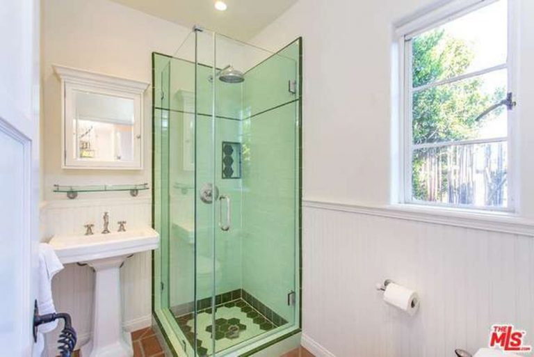 A simple yet functional bathroom with small shower area separated with a frameless glass, a pedestal sink and single casement window.