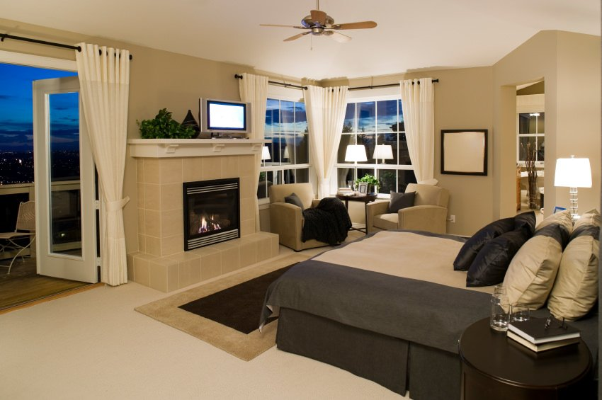 A classy master bedroom with a fireplace and a stylish bed surrounded by beige walls and white window curtains.