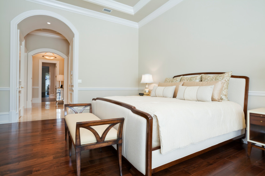 This master bedroom features a light-finished walls. The hardwood flooring matches the bed's frame.