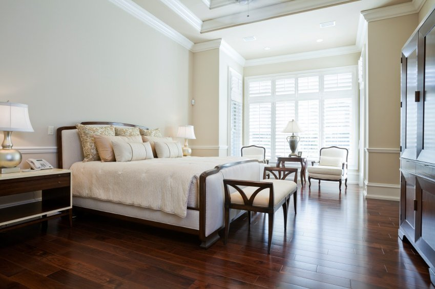 This master bedroom boasts a large bed and a coffee table set situated on top of the room's hardwood flooring.