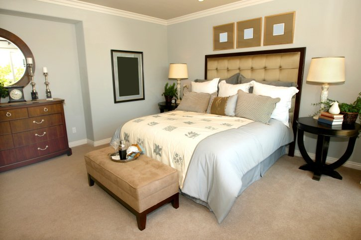 This primary bedroom features an elegant bed set on the carpet flooring. The room also has multiple stylish wall decors.