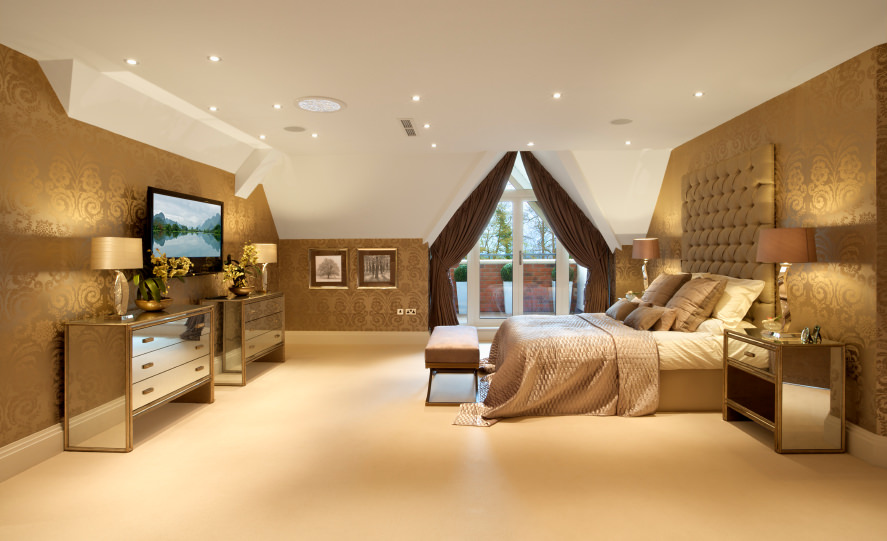A luxurious master bedroom with elegant walls and fine carpet flooring lighted by scattered recessed ceiling lights.
