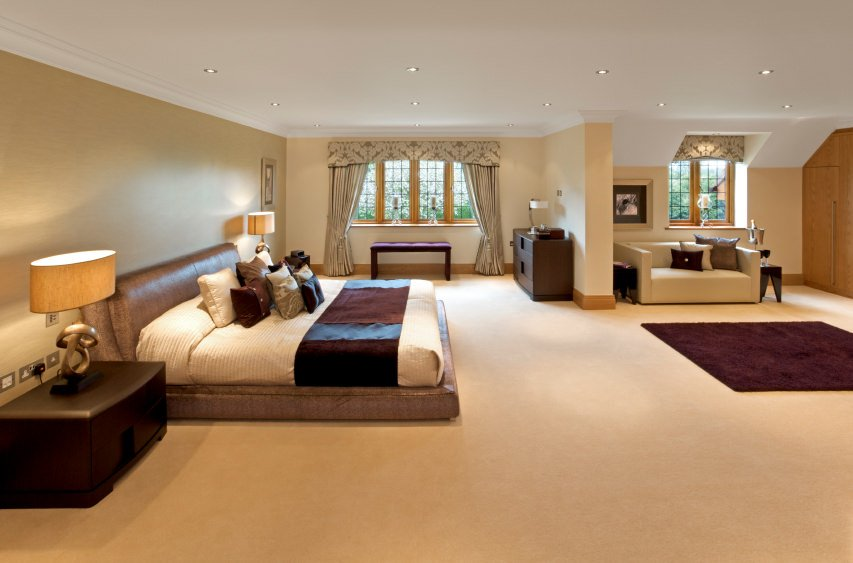 Spacious primary bedroom with a charming bed set on the carpet flooring topped by a classy rug. There's a couch near the window as well.