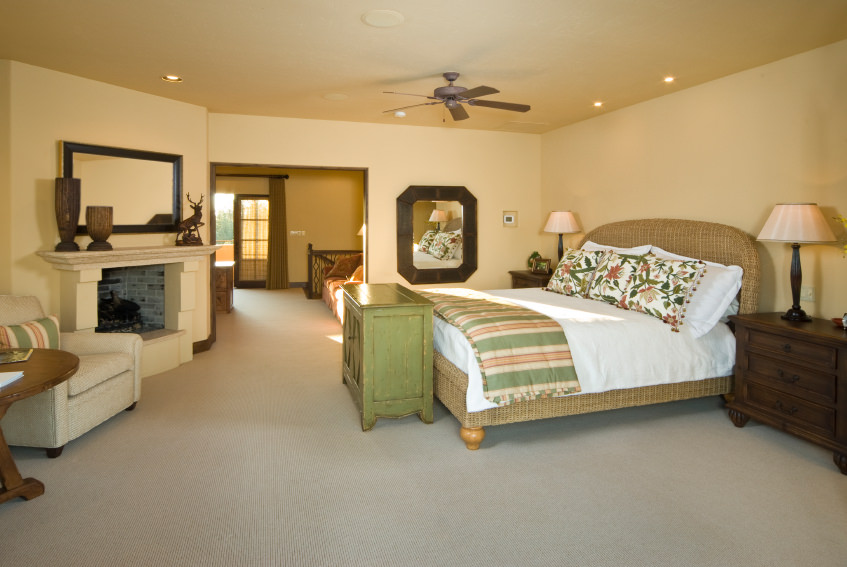 Large primary bedroom with its own sitting area and a fireplace. The room features beige walls and ceiling along with carpet flooring.