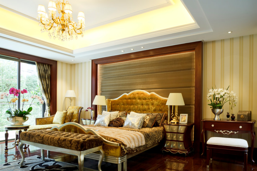 Luxury primary bedroom showcases a classy bed with a custom headboard fixed to the striped wall. It has hardwood flooring and a tray ceiling with a hanging crystal chandelier.