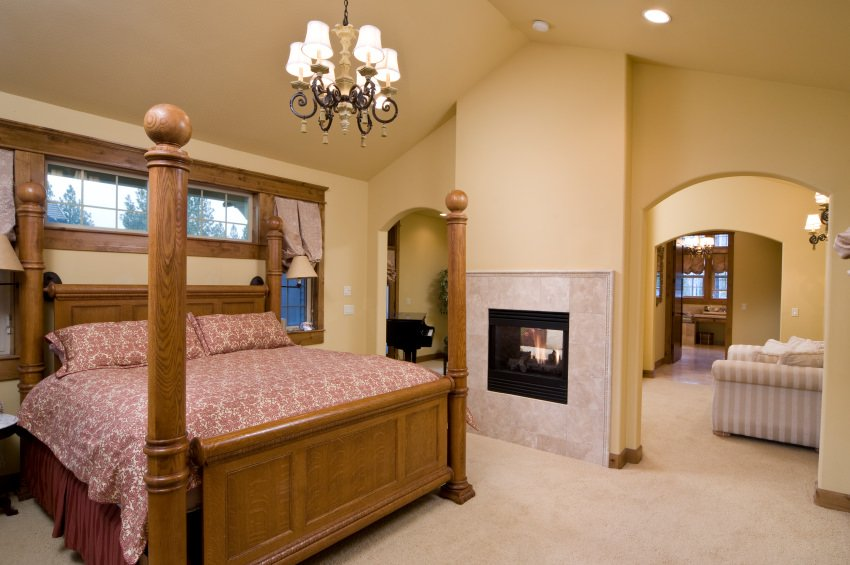 Yellow primary bedroom features a wooden four-poster bed dressed in red floral bedding along with open archways leading to the seating area. It includes a fireplace with marble surround tiles and a vintage chandelier that hung from the vaulted ceiling.
