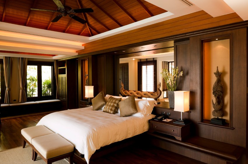 A warm primary bedroom decorated with antique sculptures placed on the inset wall niches. It has dark hardwood flooring and a wood beam ceiling with a hanging fan.