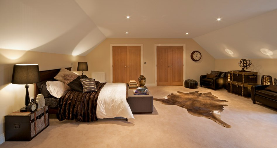 Large primary bedroom featuring carpet flooring and a shed ceiling lighted by recessed lights.