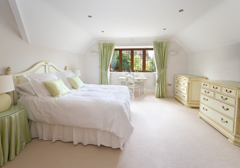 This primary bedroom boasts carpet flooring and a classy bed, along with a study desk by the windows.