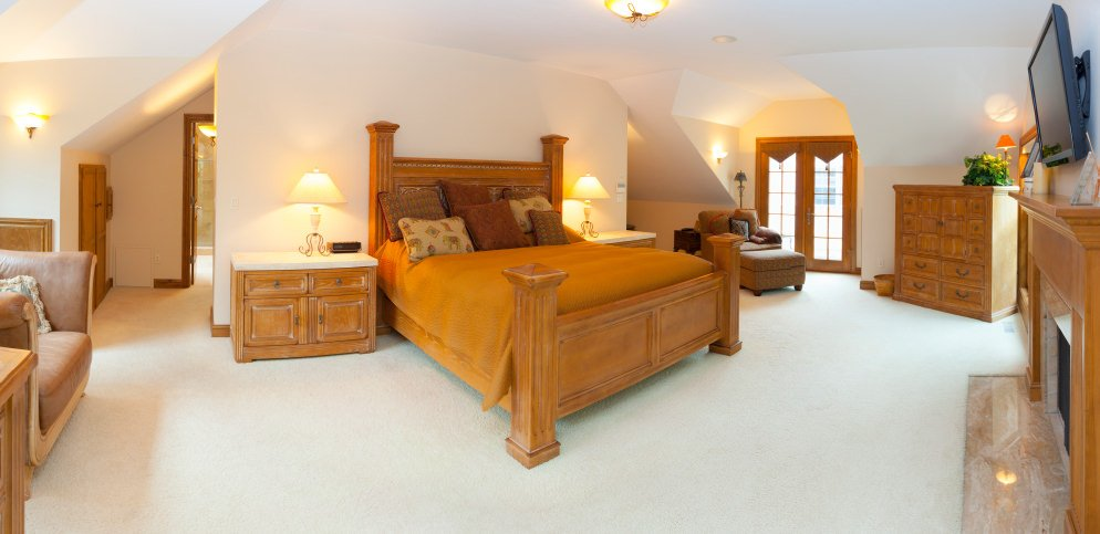 Spacious primary bedroom with rustic furniture set and warm white lighting, along with a fireplace and carpet flooring.
