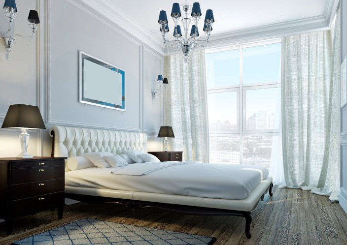 Natural light streams through the full height glass windows in this master bedroom showcasing a blue chandelier with matching sconces and white tufted bed over wood plank flooring.