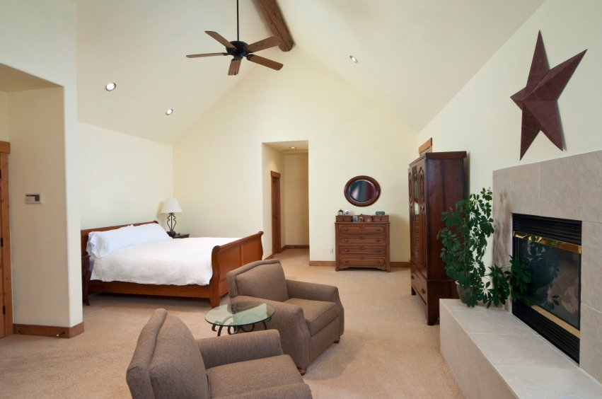 This primary bedroom offers its own sitting area with modish chairs and a coffee table near the fireplace. The room also features white walls and vaulted ceiling, along with the carpet flooring.