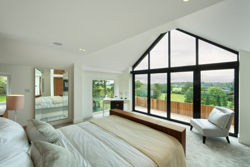 Master bedroom featuring glass windows and doors overlooking the refreshing surroundings.