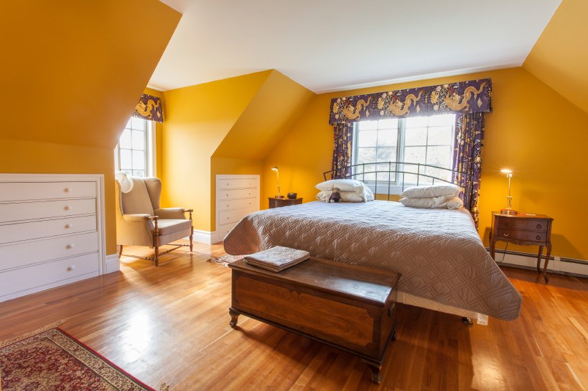 Elegant master bedroom featuring yellow walls along with elegant window curtains. The hardwood flooring looks magnificent as well.