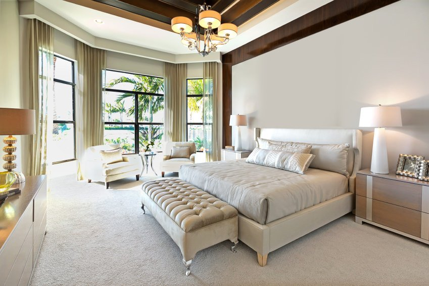 This primary bedroom boasts a classy bed set on the white carpet flooring. The room offers a sitting area near the windows. It also has a stunning ceiling lighted by an elegant ceiling light.